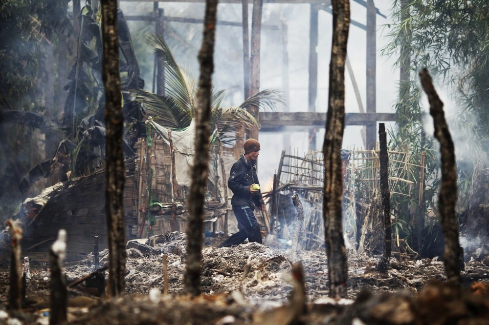 A man walks though a burnt Rohingya village during fighting between Buddhist Rakhine and Muslim Rohingya communities in Sittwe June 10, 2012. Credit: Reuters/Staff