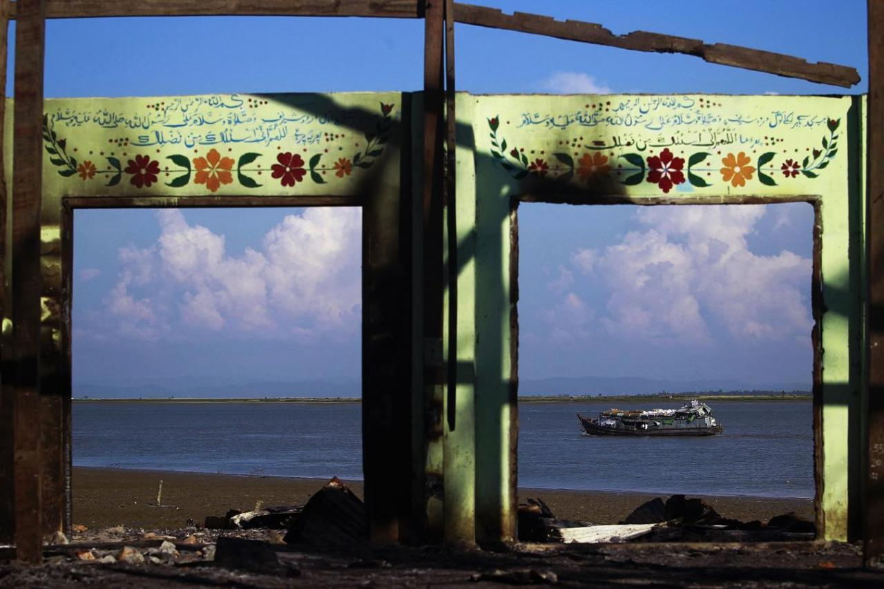 A boat is framed by the ruins of a destroyed mosque in a part of Pauktaw township that was burned in recent violence, in this October 27, 2012 file picture. Credit: Reuters/Soe Zeya Tun