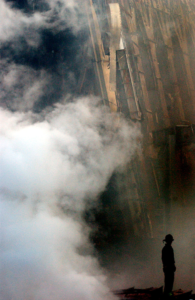 A solitary firefighter stands amid the rubble and smoke in New York City. Credit: Wikimedia Commons