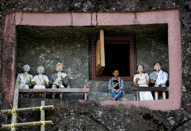 """A visitor sits outside a burial chamber cut into a massive boulder of Loko'mata, a traditional Toraja burial site, during an ancient Torajan ritual known as """"Ma'nene"""", near Rantepao, North Toraja, South Sulawesi, Indonesia, September 11, 2017. Credit: Reuters"""