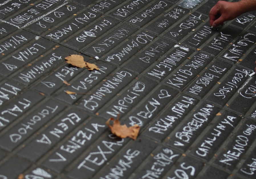A person writes messages on a sidewalk at Las Ramblas in Barcelona after terrorist attacks in the city. Credit: Reuters