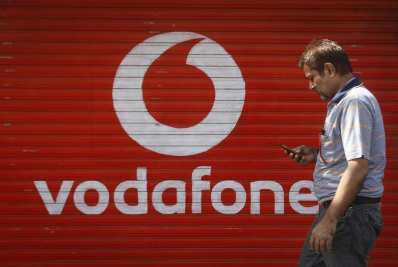 A man checks his mobile phone as he walks past a shop displaying the Vodafone logo on its shutter in Mumbai January 15, 2014. Credit: Reuters/Danish Siddiqui