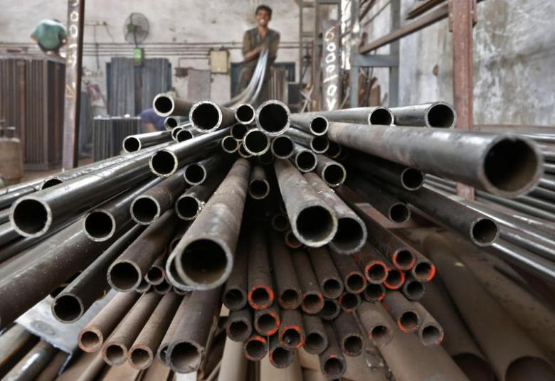 A worker stacks steel pipes in Ahmedabad. Credit: Reuters/Amit Dave