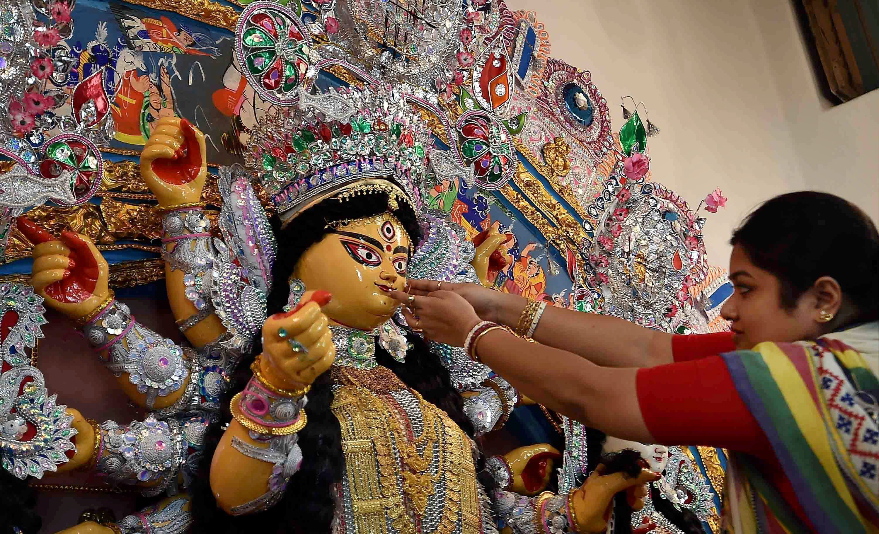 An idol of Goddess Durga being being decorated with gold ornaments during Durga Puja festival in Kolkata on Tuesday. Credit: PTI/Ashok Bhaumik