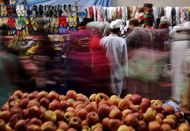 Shoppers crowd at a roadside market next to a handcart loaded with apples for sale in New Delhi, India, November 13, 2015. Credit: Reuters/Anindito Mukherjee/File Photo