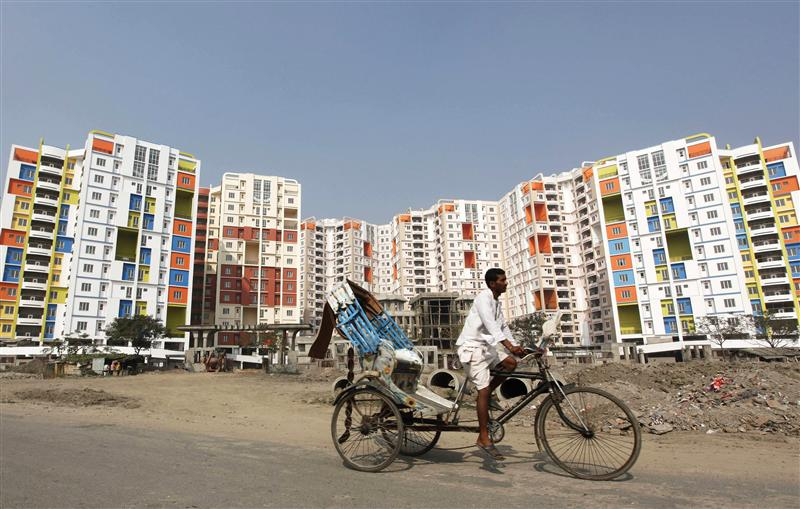 A man rides his cycle rickshaw past newly-constructed residential buildings on the outskirts of Kolkata December 29, 2010. Credit: Reuters/Rupak De Chowdhuri
