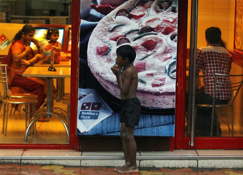 A homeless boy holds biscuits that he received as alms as he takes shelter from rain in front of a fast food shop in Mumbai November 11, 2009. Credit: Reuters/Arko Datta
