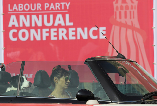 A woman drives past the Labour party Conference venue with a dog on the back seat of her car in Brighton, Britain, September 24, 2017. Credit: Reuters