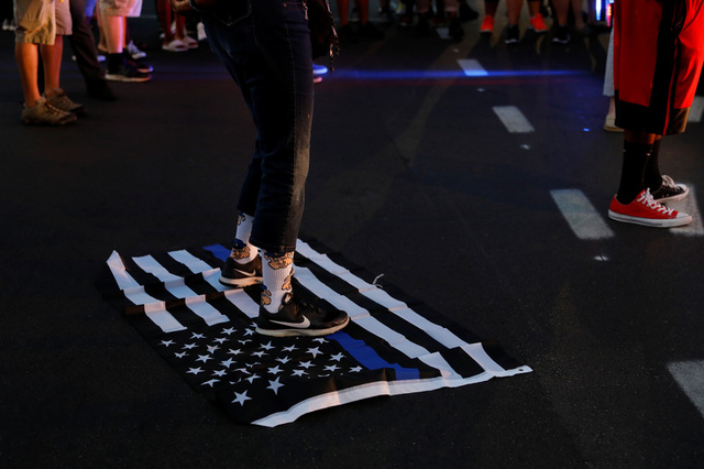 """A protester stands on a """"blue lives matter"""" flag after the not guilty verdict in the murder trial of Jason Stockley, a former St. Louis police officer, charged with the 2011 shooting of Anthony Lamar Smith, who was black, in St. Louis, Missouri, U.S., September 15, 2017. Credit: Reuters"""