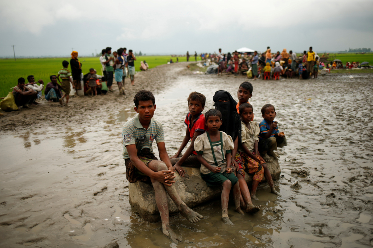 Rohingya refugees sit as they are temporarily held by the Border Guard Bangladesh (BGB) in an open area after crossing the border, in Teknaf, Bangladesh, September 3, 2017. Credit: Reuters/Mohammad Ponir Hossain