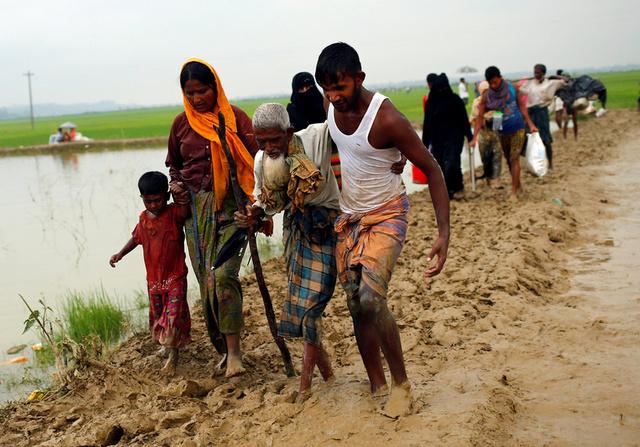 Rohingya refugees walk on the muddy path after crossing the Bangladesh-Myanmar border in Teknaf, Bangladesh, September 3, 2017. Credit: Reuters