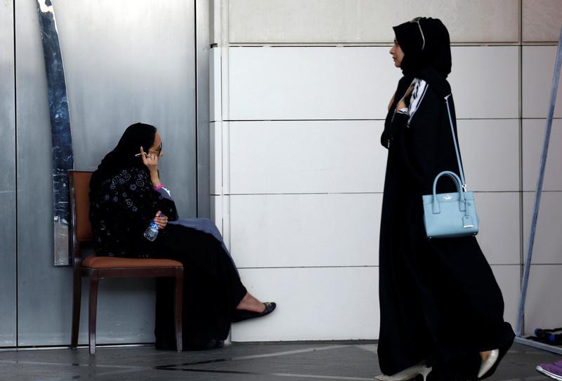 A Saudi woman speaks on the phone as another woman walks past her in Riyadh, Saudi Arabia. Credit: Reuters/Faisal Al Nasser
