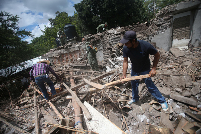 Soldiers and residents clear rubble from a destroyed house after an earthquake in San Juan Pilcaya, at the epicenter zone, Mexico, September 25, 2017. Credit: Reuters