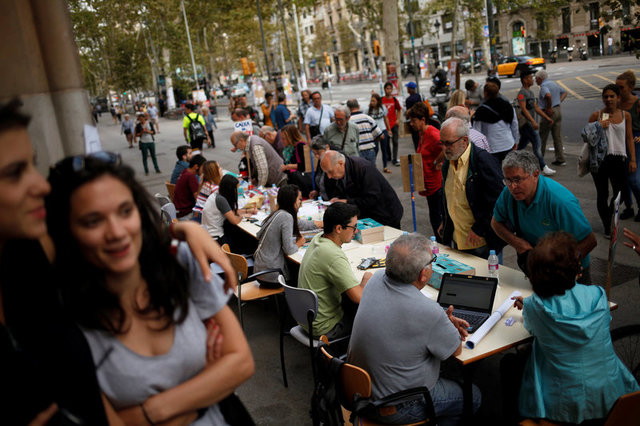 Students and volunteers inform citizens about the banned October 1 independence referendum outside the University of Barcelona, in Barcelona, Spain, September 26, 2017. Credit: Reuters