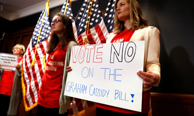 Women hold signs during a press conference held by U.S. Sen. Bob Casey, D-Pa., to speak out against the latest Republican effort to repeal Obamacare on Capitol Hill in Washington, U.S., September 25, 2017. Credit: Reuters