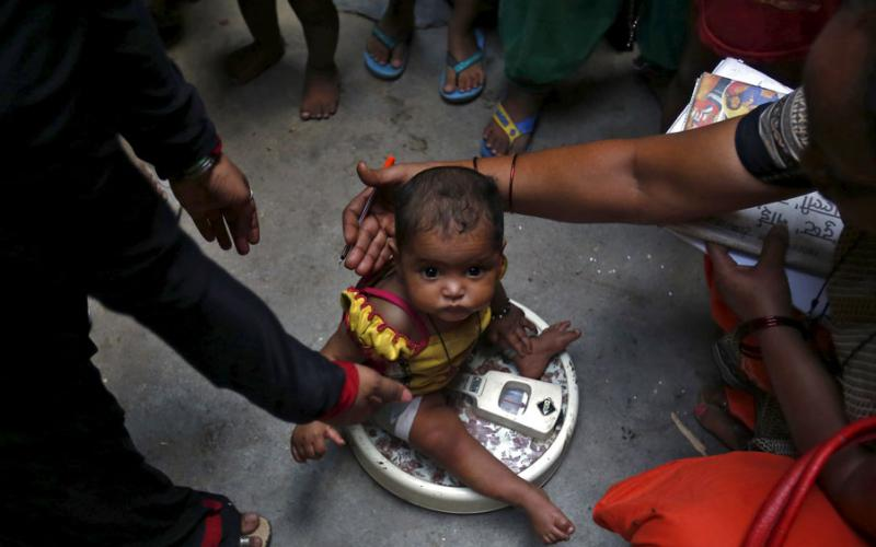 A health worker (R) weighs a child under a government program in New Delhi, India