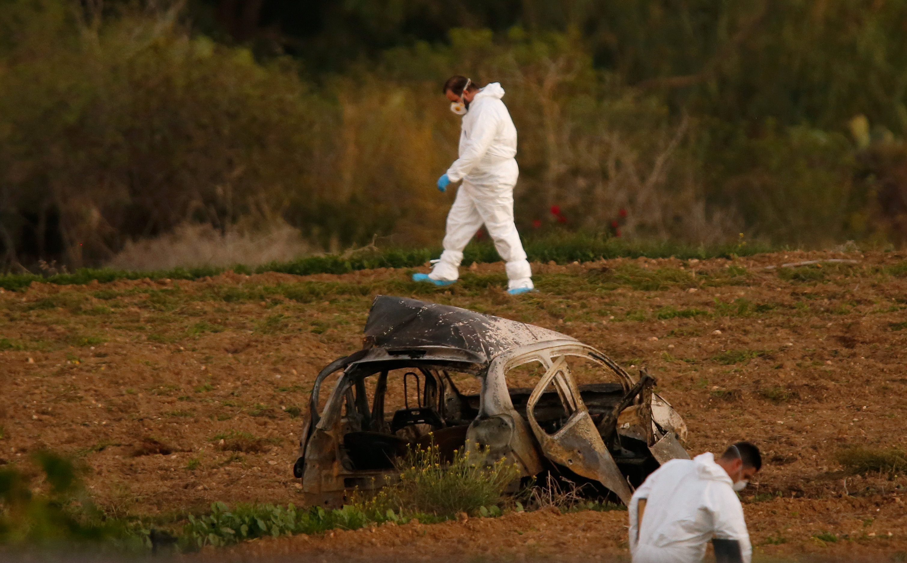 Forensic experts walk in a field after a powerful bomb blew up a car (Foreground) and killed investigative journalist Daphne Caruana Galizia in Bidnija, Malta, October 16, 2017. Credit: Reuters/Darrin Zammit Lupi