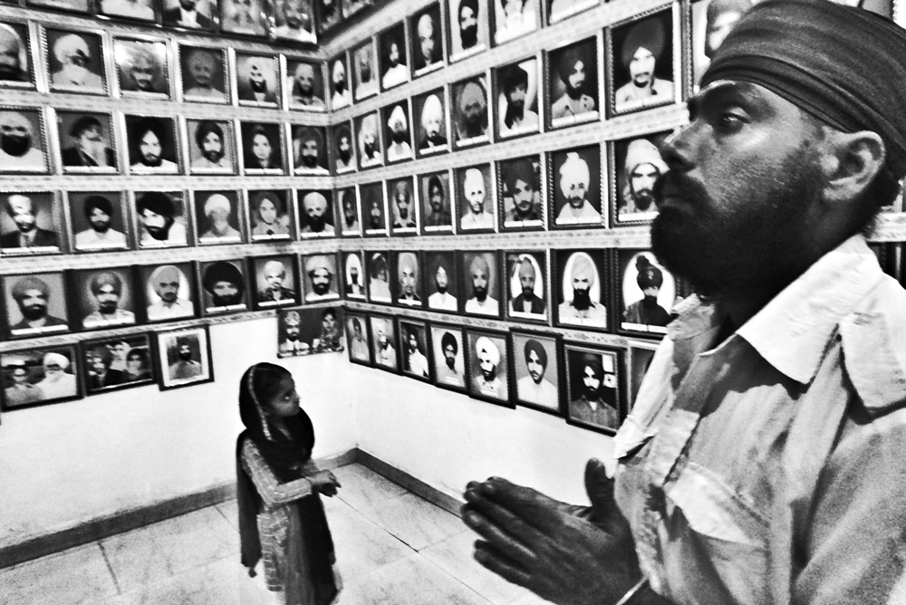 A girl and her father pray at the martyrs' museum in Tilak Vihar, New Delhi.