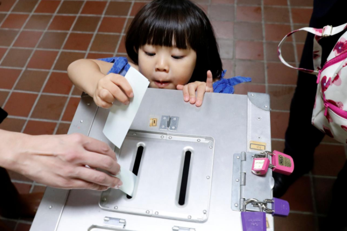 A girl casts her father's ballot for a national election at a polling station in Tokyo, Japan October 22, 2017. Credit: Reuters/Kim Kyung-Hoon