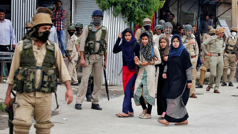 Women walk past police during clashes with stone pelters in Srinagar