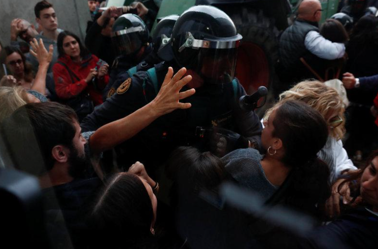 Scuffles break out as Spanish Civil Guard officers force their way through a crowd and into a polling station for the banned independence referendum. Credit: Reuters
