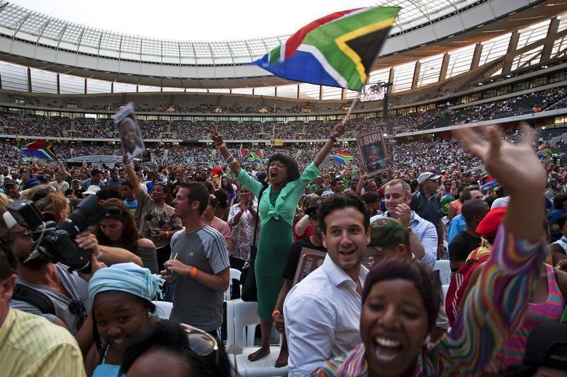 """A woman flies a South African flag during the """"Nelson Mandela: A Life Celebrated"""" memorial service at Cape Town Stadium December 11, 2013. Credit: Reuters"""