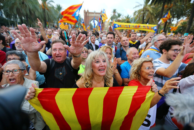 People react as they watch a session of the Catalonian regional parliament on a giant screen at a pro-independence rally in Barcelona, Spain, October 10, 2017. Credit: Reuters
