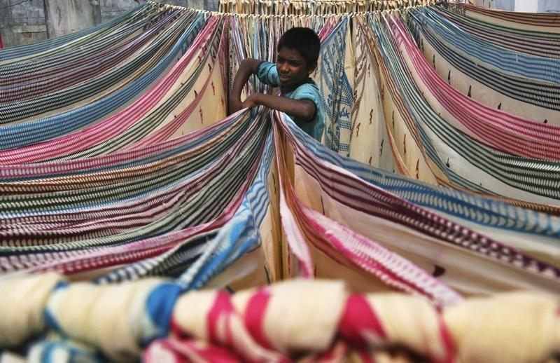 A boy separates starched sarees left to dry on the roof of a cotton factory in Hyderabad, November 30, 2012. REUTERS/Krishnendu Halder/Files