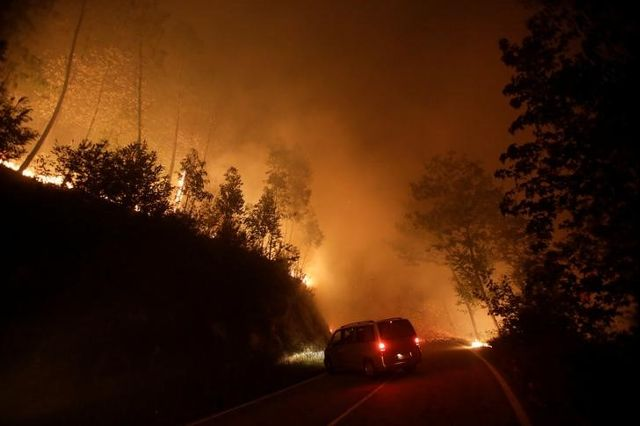 A vehicle turns around as a forest fire burns by the road near Vigo, Spain, October 15, 2017. Credit: Reuters