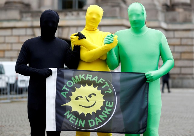 """Environmental activists pose for photographers near the German Parliamentary Society offices during the exploratory talks about forming a new coalition government held by CDU/CSU in Berlin, Germany, October 26, 2017. The words read """"Nuclear power? No thank you."""" Credit: Reuters"""