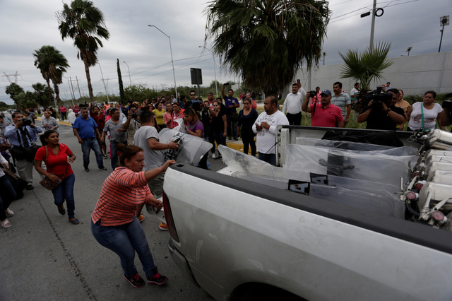 Relatives of inmates grab police shields from a truck arriving at Cadereyta state prison after a riot broke out at the prison, in Cadereyta Jimenez, on the outskirts of Monterrey, Mexico October 10, 2017. Credit: Reuters