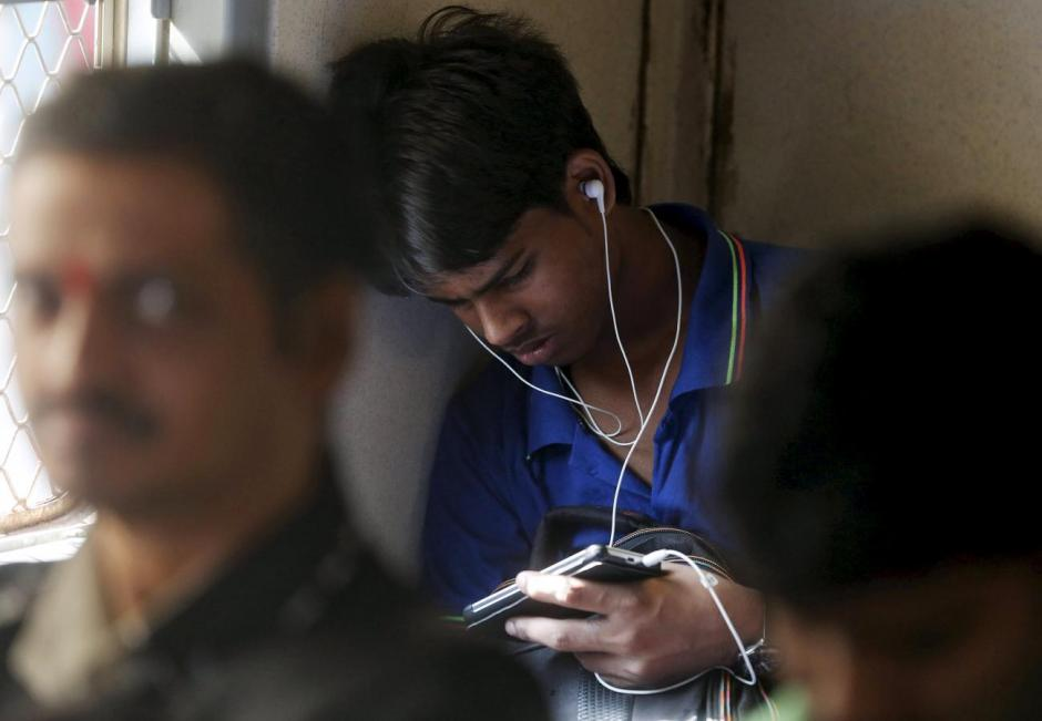A man watches a video on his mobile phone as he commutes by a suburban train in Mumbai, India, March 31, 2016. Credit: Reuters/Shailesh Andrade