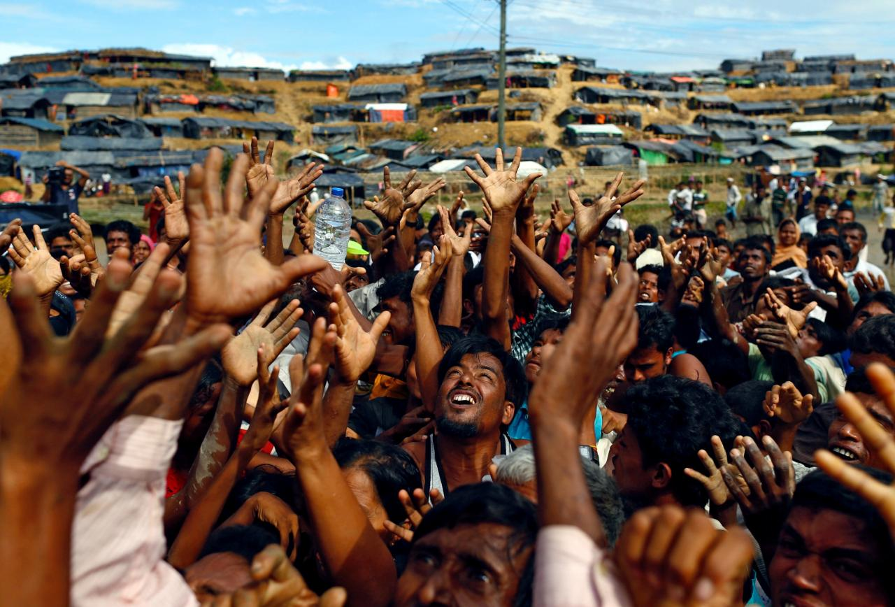Rohingya refugees stretch their hands to receive aid distributed by local organisations at Balukhali makeshift refugee camp in Cox's Bazar, Bangladesh, September 14, 2017. REUTERS/Danish Siddiqui