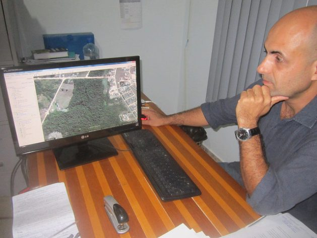 Pedro Correa, director of the environment in the Paranaita city government, looks at a photo of the city surrounded by forests, on his computer screen. Originally from the southern state of São Paulo, he worked for a few months on the construction of the Teles Pires hydropower dam and decided to stay in this town because he likes the quality of life. Credit: IPS