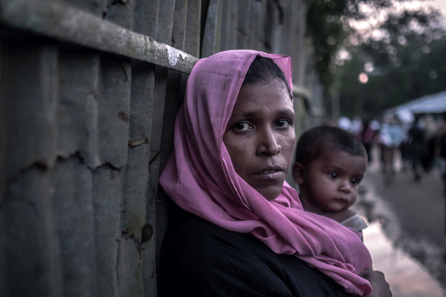 Razida, 35 carries her ten month old son Anisul through Unchiprang Camp in Bangladesh. Razida arrived in Bangladesh 20 days ago after walking for six days with her eight children. She brought nothing with her when she fled Myanmar and had to ask for food from people on the way. Credit:Oxfam