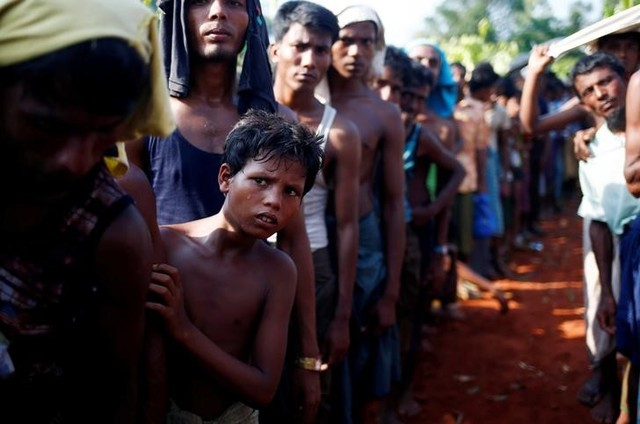 A Rohingya refugee boy looks on as he stands in a queue to receive relief supplies given by local people in Cox's Bazar, Bangladesh September 16, 2017. Credit: Reuters