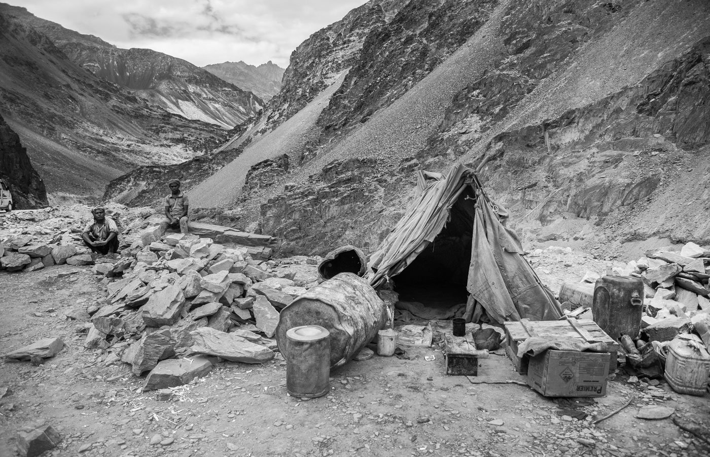 Jiten Murmu (left) from Bihar, with a co-worker, waiting outside their tent near Chilling village for lunch to arrive from another camp site. The canvas tents barely protect the workers during the cold nights. They camp by the roadside and follow the road works as they advance.