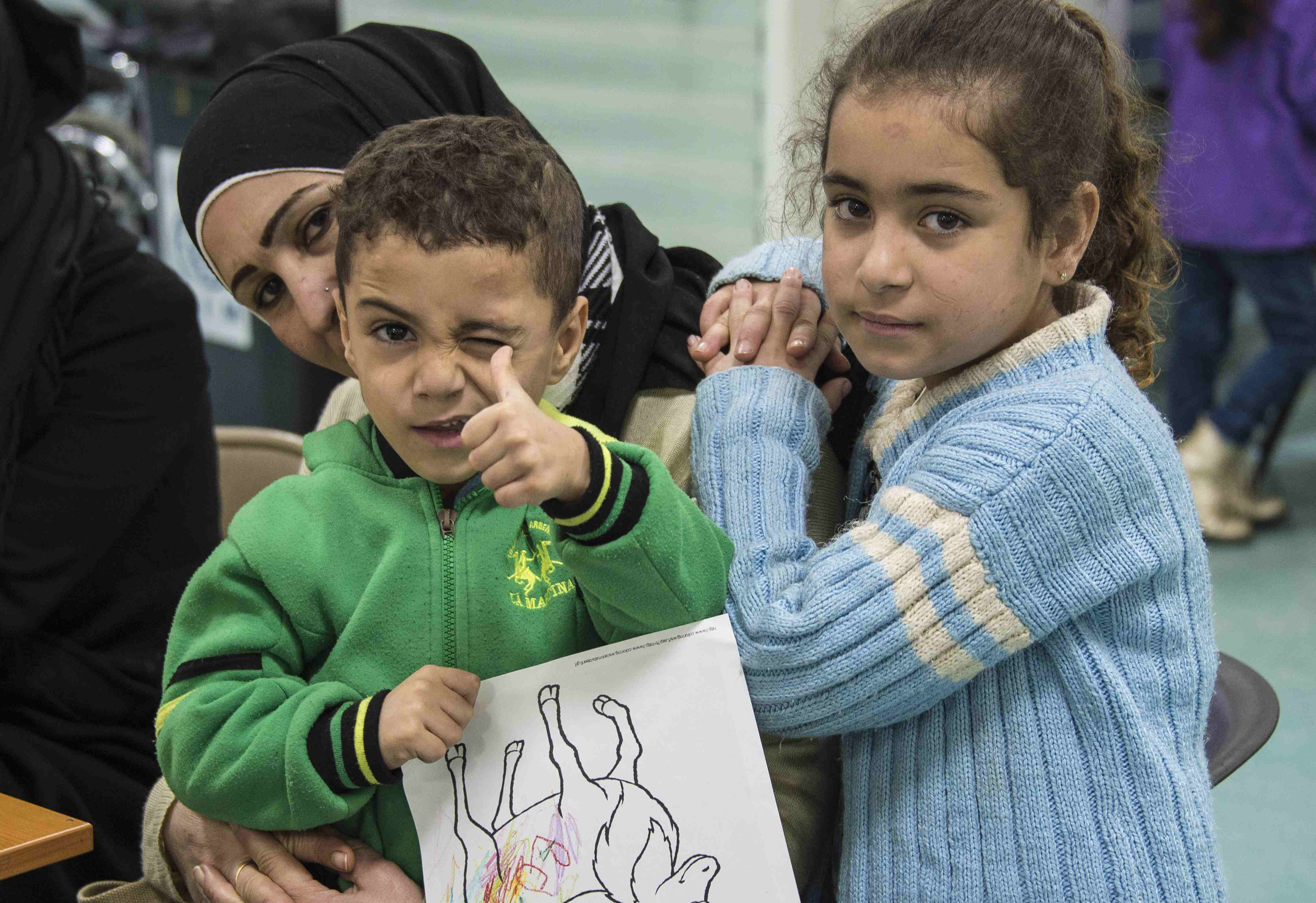 Two Syrian refugee children pose while their family undergoes medical screening before the beginning of an airlift to Canada, in Beirut, Lebanon December 9, 2015. The first plane load of Syrian refugees departed from Beirut on Thursday, aboard a military aircraft bound for Toronto. The Liberal government plans to resettle 10,000 refugees from Syria's four-year-old civil war by the end of the year and a further 15,000 by the end of February. Picture taken December 9, 2015. Credit: Reuters/Corporal Darcy Lefebvre/Canadian Forces Combat Camera/Handout via Reuters