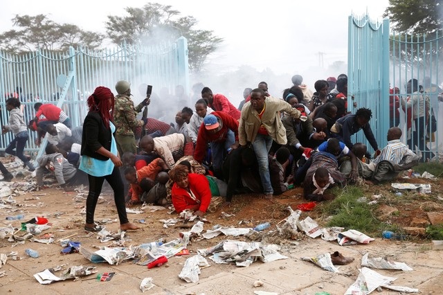 People fall as police fire tear gas to try control a crowd trying to force their way into a stadium to attend the inauguration of President Uhuru Kenyatta at Kasarani Stadium in Nairobi, Kenya November 28, 2017. Credit: Reuters/Baz Ratner