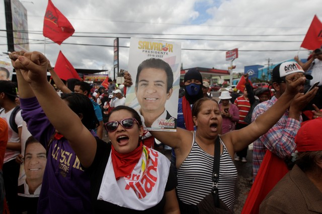 Supporters of Salvador Nasralla, presidential candidate for the Opposition Alliance Against the Dictatorship, sing the national anthem, while waiting for official presidential election results outside the warehouse of the Supreme Electoral Tribunal in Tegucigalpa, Honduras November 29, 2017. Credit: Reuters/Jorge Cabrera