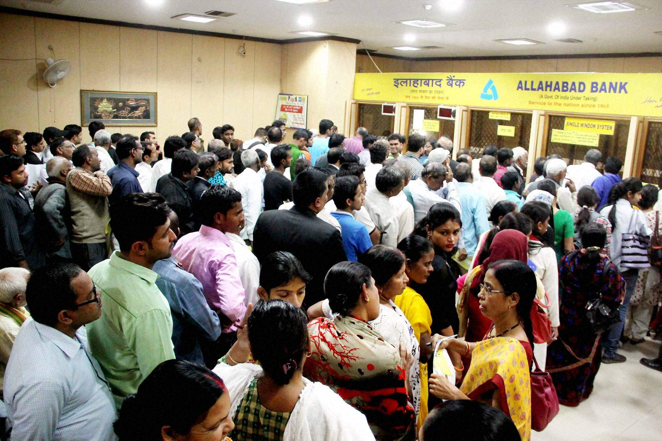 People wait in queues in a bank to exchange their 500 and 1000 currency notes in Allahabad