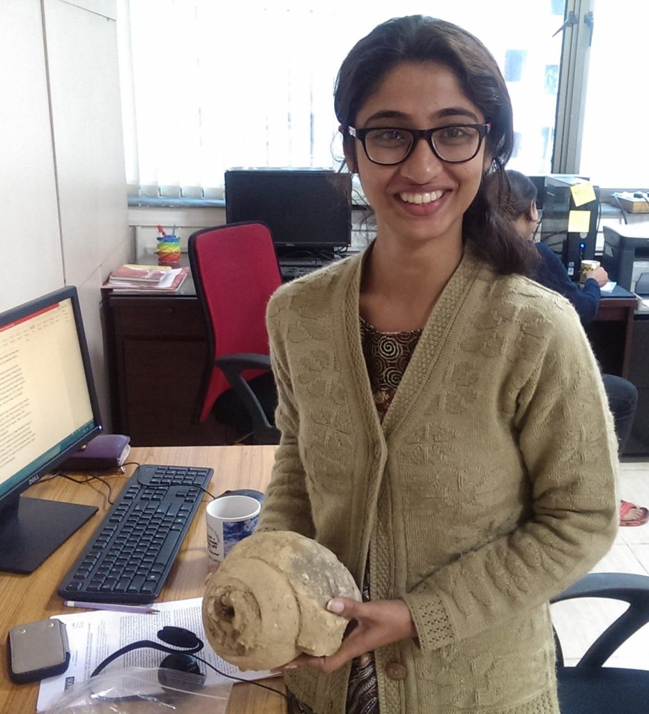 A researcher in Devapriya's team poses with a mollusc fossil.