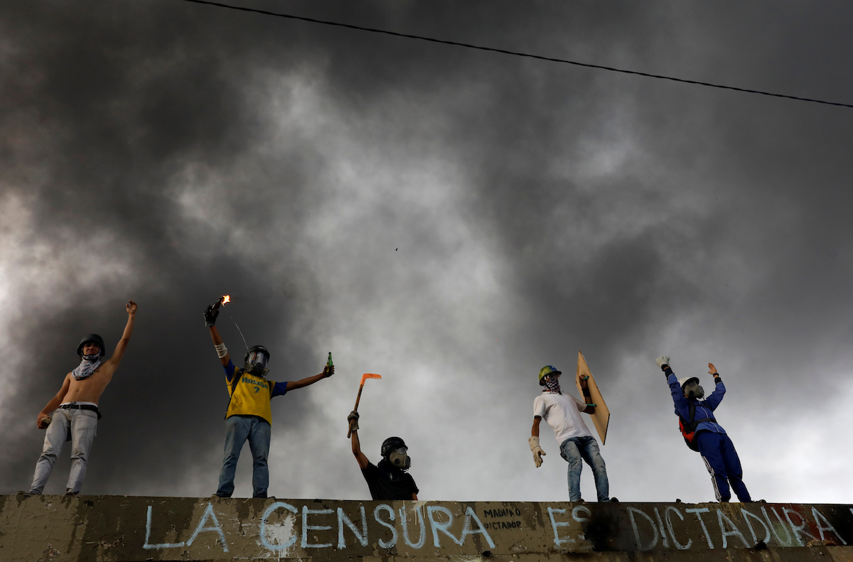 "Demonstrators gesture to riot security forces while rallying against President Nicolás Maduro over graffiti that reads ""censorship is dictatorship"" in Caracas, Venezuela, May 2017 Carlos Garcia Rawlins/Reuters"
