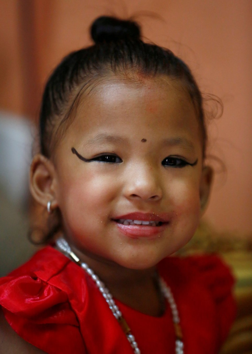 Newly appointed living goddess, three-year-old Kumari Trishna Shakya, smiles while being pictured before being taken to the Kumari house from her private residence in Kathmandu, Nepal September 28, 2017. Credit: Reuters