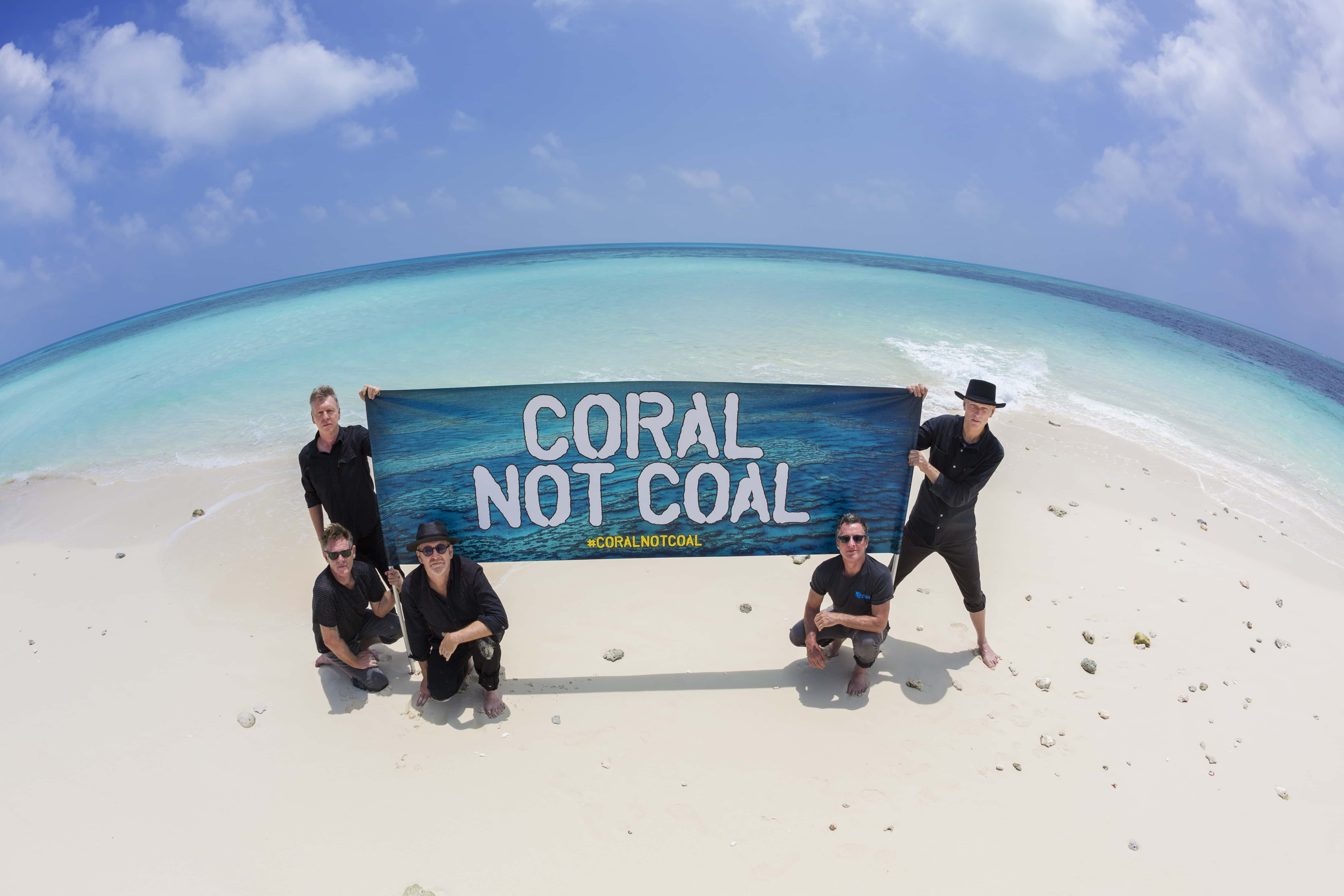 "Australian rock band Midnight oil holds up a ""Coral not Coal' banner. Credit: StopAdaniAlliance."
