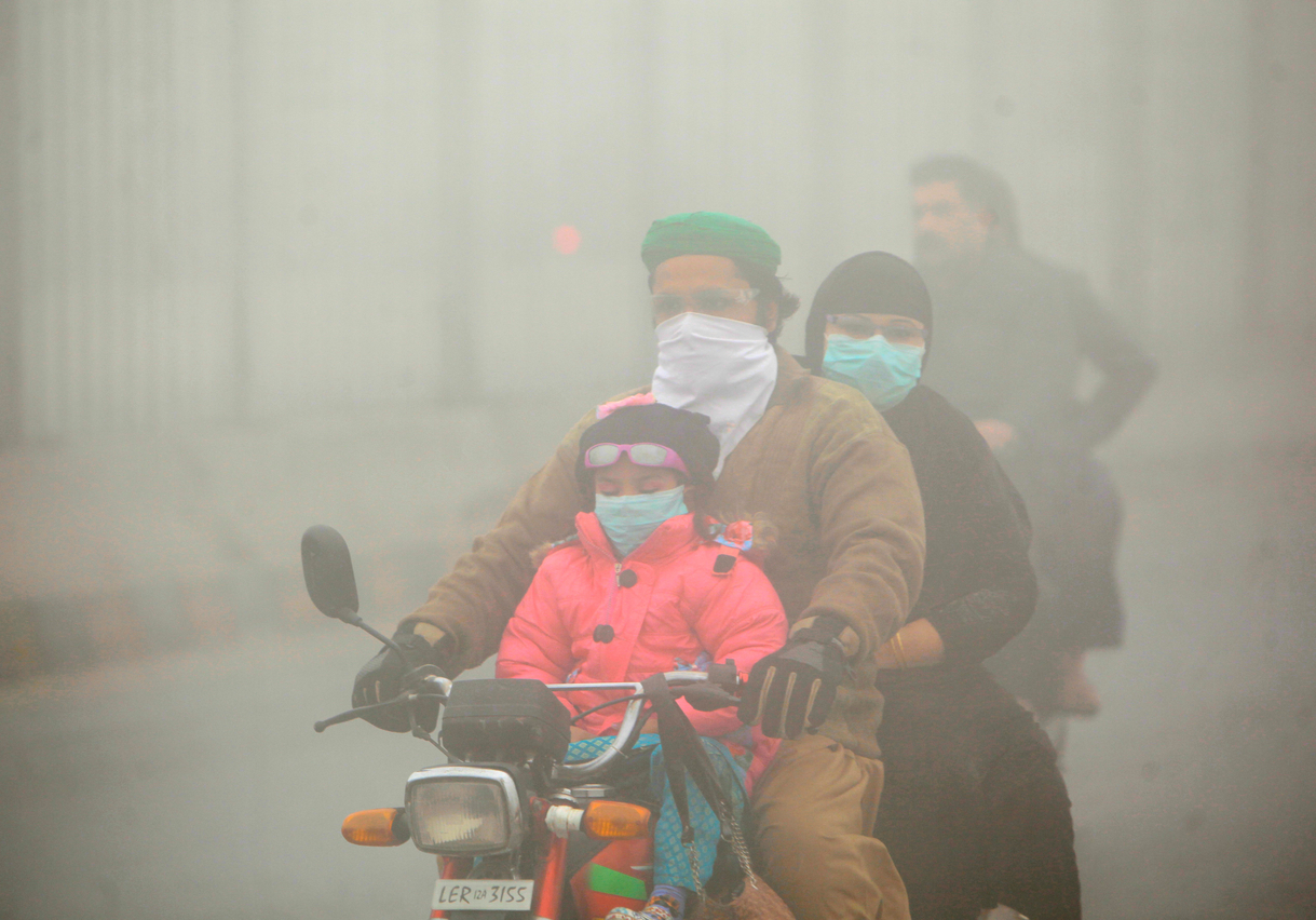 People use face masks to protect themselves from morning smog as they ride on bike along a road in Lahore, Pakistan November 10, 2017. Credit: Reuters