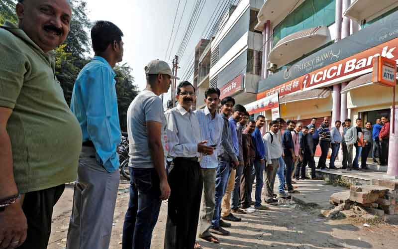 People stand in queue to withdraw from an ATM post demonetisation in November 2016. Credit: Reuters