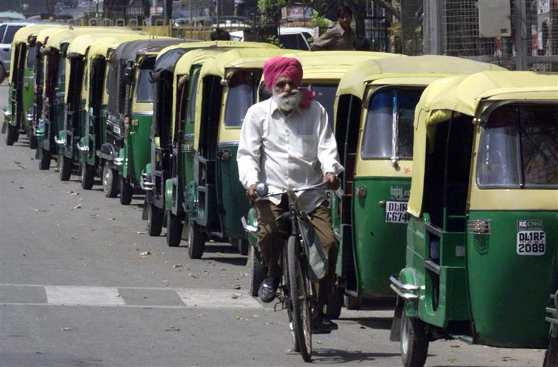 A cyclist passes by a queue of auto-rickshaws waiting to fill their tanks at station selling compressed natural gas in New Delhi April 2, 2001. Credit: Reuters