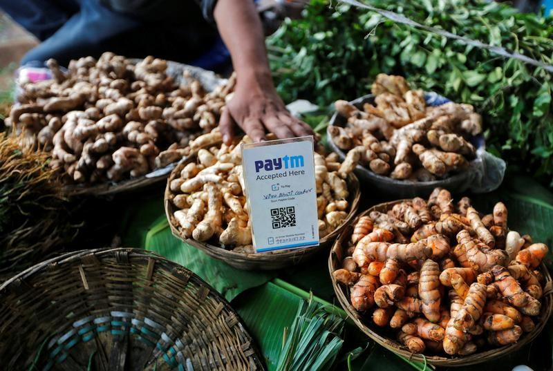 An advertisement board displaying a QR code for Paytm, a digital wallet company, is seen placed amidst vegetables at a roadside vendor's stall in Mumbai, India, November 19, 2016. Picture taken November 19, 2016. Credit: Reuters/Shailesh Andrade/File Photo