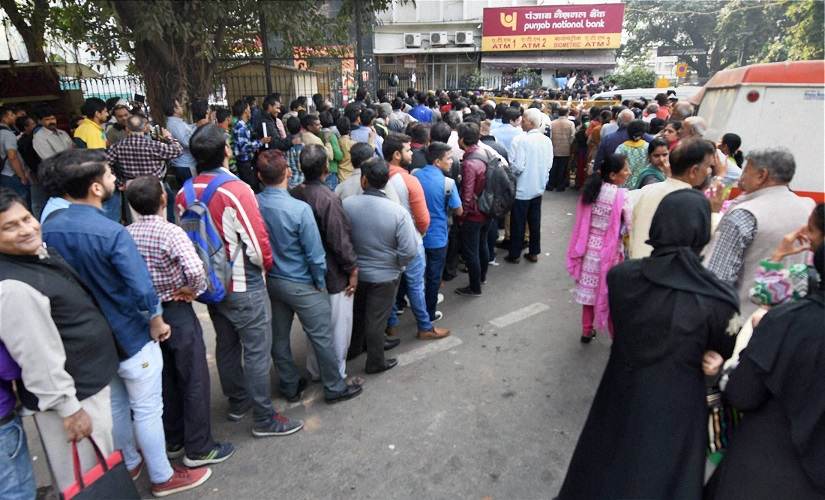People standing in long queues to exchange their old Rs 500 and 1000 notes and withdraw cash from the ATM in New Delhi. Credit: PTI/Subhav Shukla/Files